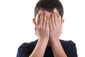 Boy covering eyes with hands