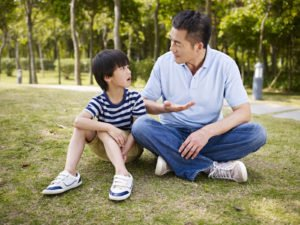 asian father and elementary-age son sitting on grass outdoors having a serious conversation.