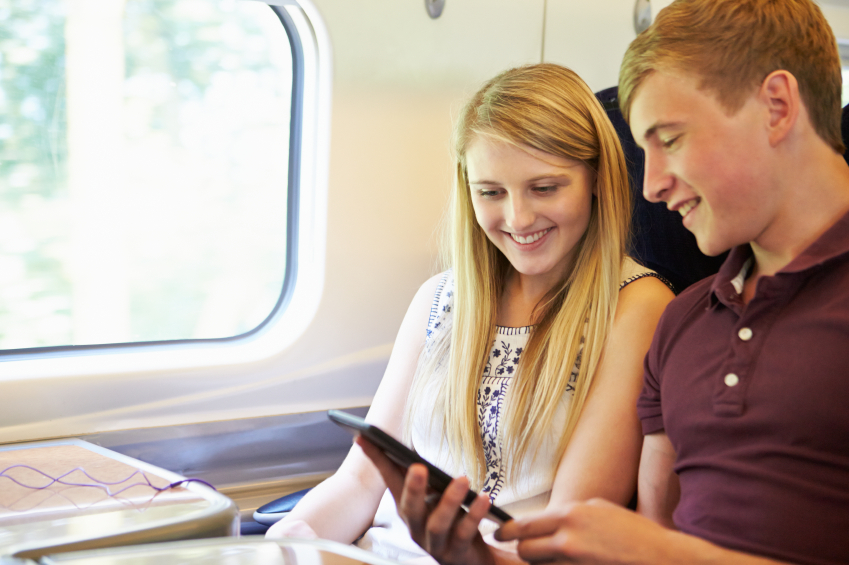 Young Couple Reading E Book On Train Journey