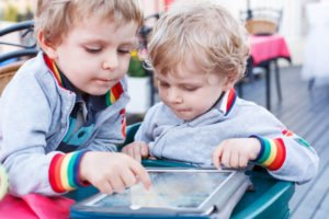 Two little sibling boys having fun together with tablet pc