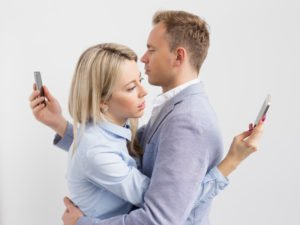 Couple embracing and still using their mobile phones